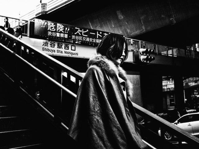 contraste photographique d'une femme en fourrure descendant les marches à Tokyo