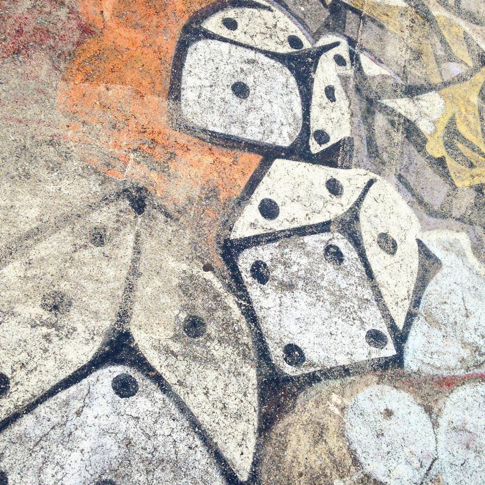 street art sur le sol d'un skatepark, peinture de dés géants lancés sur fond orange, jaune et mauve