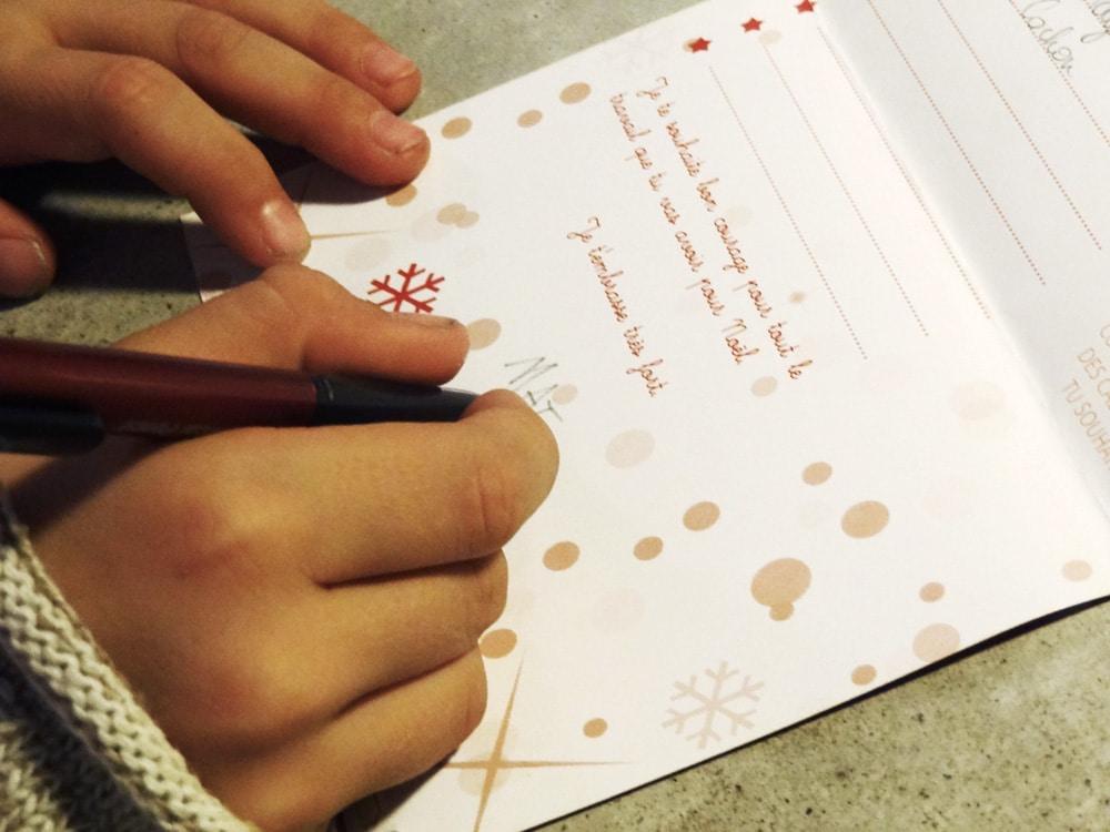 enfant écrivant sa lettre au papa noel