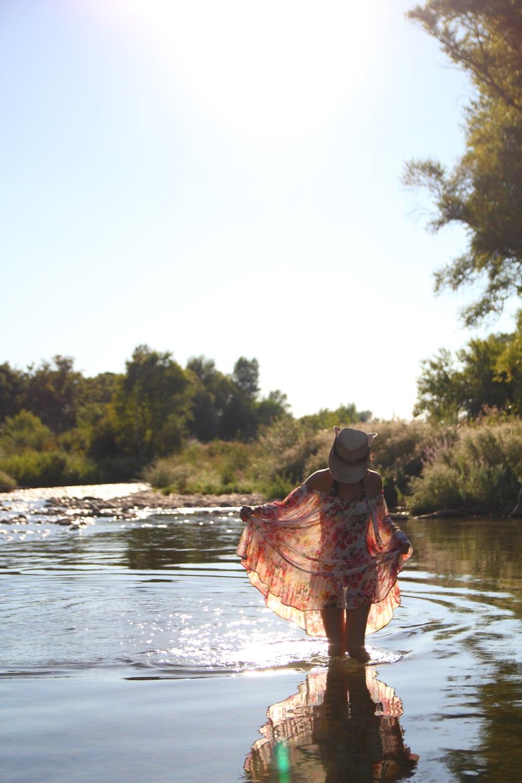 femme mode dans la rivière en robe legère à fleurs