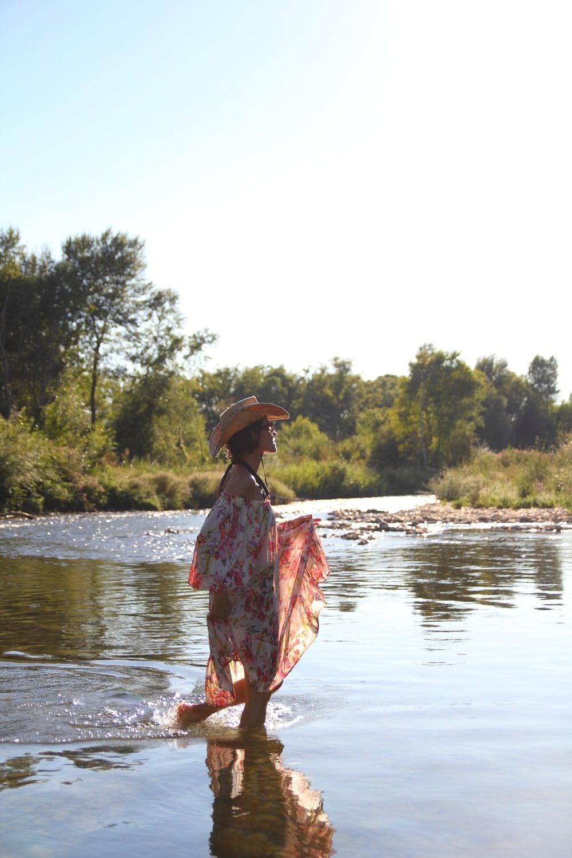 femme marchant dans l'eau en robe fleurie mode